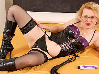 Golden-haired granny in a dominatrix outfit masturbates in her daybed