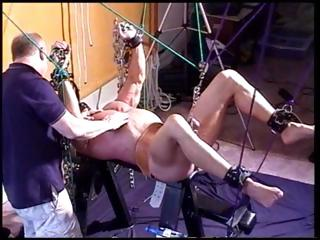 Muscular guy gets chained-up and his balls and cock are restrained as well